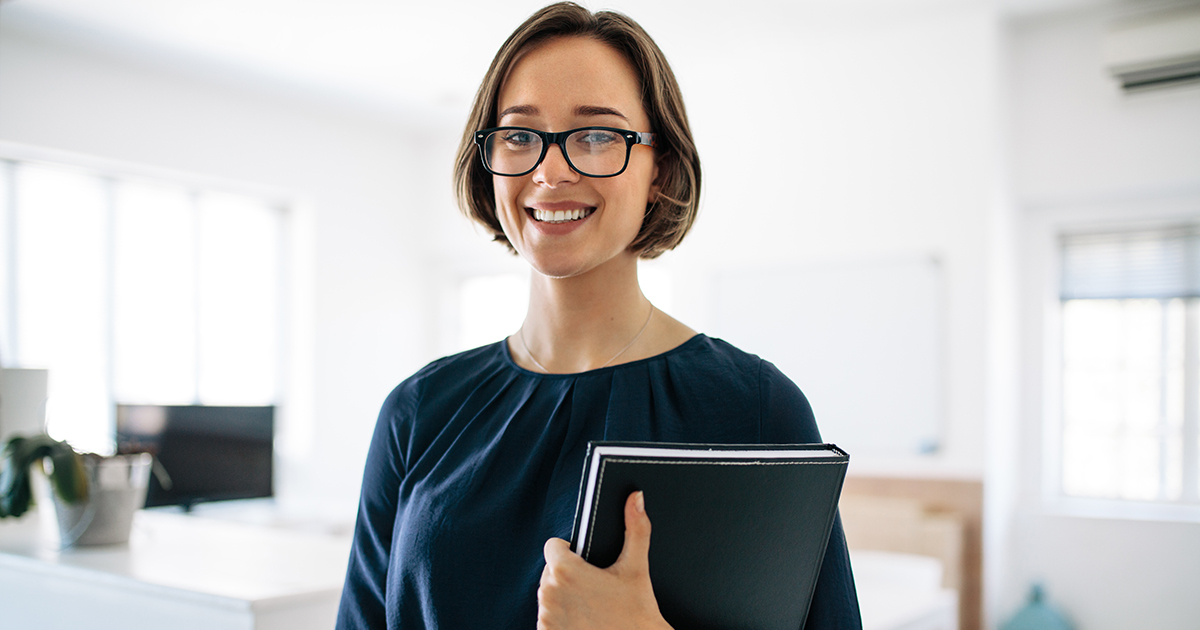 Smiling businesswoman wearing spectacles standing in office holding a diary. Portrait of a happy woman entrepreneur at work.